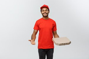 Delivery Concept - Portrait of Happy African American delivery man pointing hand to present a pizza box package. Isolated on Grey studio Background. Copy Space.