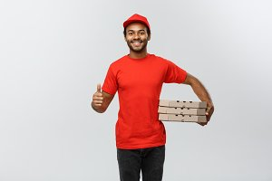 Delivery Concept - Portrait of Happy African American delivery man holding box packages and showing thumps up. Isolated on Grey studio Background. Copy Space.