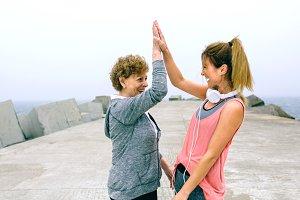 Senior sportswoman and female friend high five