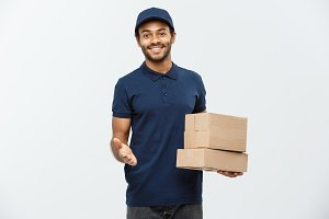 Delivery Concept - Portrait of Happy African American delivery man pointing hand to present box packages. Isolated on Grey studio Background. Copy Space.