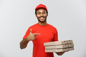 Delivery Concept - Portrait of Happy African American delivery man pointing hand to present pizza box packages. Isolated on Grey studio Background. Copy Space.