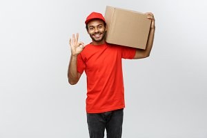 Delivery Concept - Portrait of Happy African American delivery man holding a box package and showing ok sign. Isolated on Grey studio Background. Copy Space.