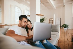 Loving young couple using laptop