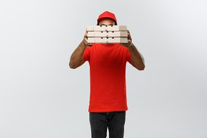 Delivery Concept - Portrait of Handsome African American Pizza delivery man hiding behide Pizza boxes. Isolated on Grey studio Background. Copy Space.