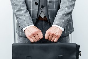 Close up of a man in suit holding briefcase