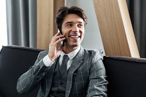 Handsome smiling businessman in suit talking on mobile phone