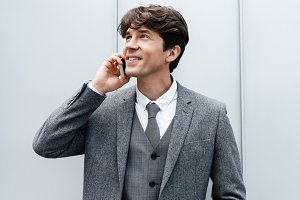 Smiling happy businessman in suit having a mobile phone conversation