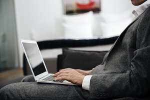 Businessman in suit with a laptop on his lap
