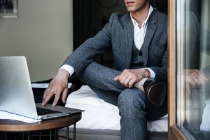 Cropped image of a businessman sitting on a bed