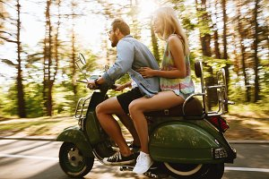 Bearded man on scooter with girlfriend outdoors