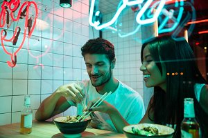 Multiethnic smiling loving couple sitting in cafe eating.