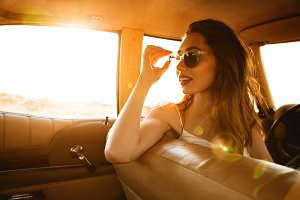 Beautiful young woman in sunglasses sitting on a front seat