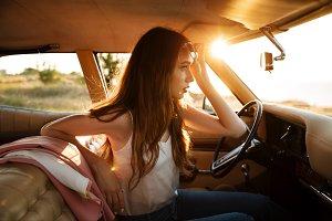 Young pretty woman in sunglasses sitting in a retro car