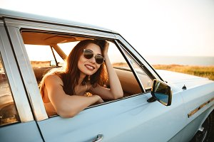 Happy young woman in sunglasses leaning on a window