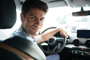 Handsome smiling male customer testing his new car