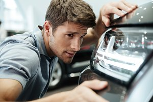 Male customer examining and looking carefully at a new car