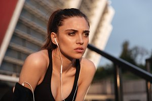 Concentrated serious young sports woman sitting with earphones