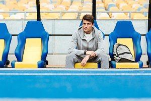 Young male athlete in sportswear sitting on a stadium seats