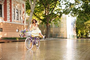 Happy lady outdoors on bicycle. Looking camera.