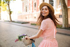 Smiling happy girl in dress and hat riding retro bicycle