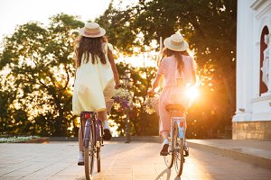 Back view image of two young ladies on bicycles.