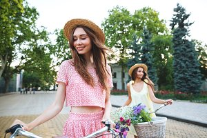Two young happy ladies standing outdoors with bicycles
