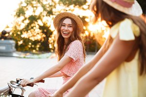 Two pretty smiling girls on a bicycle ride