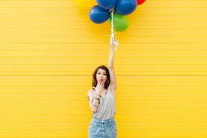 Woman standing over yellow wall. Have fun with balloons.