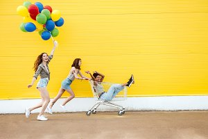 Smiling women friends have fun with shopping trolley and balloons.