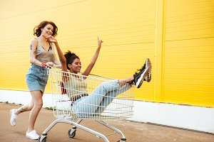 Smiling women friends have fun with shopping trolley.