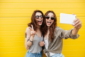 Young happy women friends standing over yellow wall make selfie