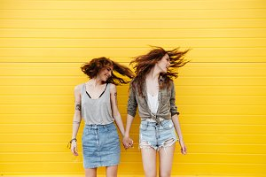 Young smiling women friends standing over yellow wall shaking hair.