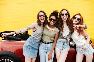 Happy emotional four young women friends standing near car