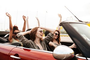 Happy emotional four young women friends sitting in car