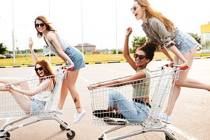 Young amazing women friends have fun with shopping trolleys.