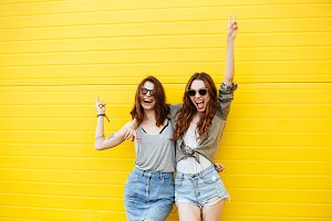 Cheerful women friends standing over yellow wall.