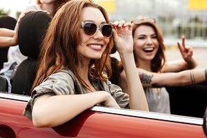 Two smiling happy girls in sunglasses having fun ride