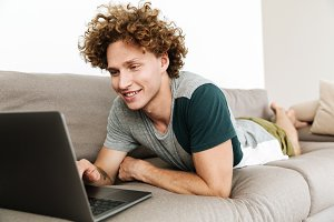 Handsome cheerful man lies on sofa using laptop computer