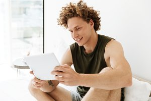 Happy man sitting on bed at home using tablet computer
