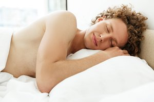 Attractive young man with curly hair sleeping in bed