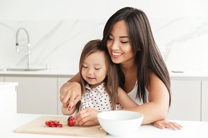 Happy young mom with little cute asian daughter cut strawberry