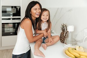 Young pretty asian woman and her daughter laughing