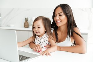 Smiling asian mother sitting at the table with her little daughter and using laptop together at home