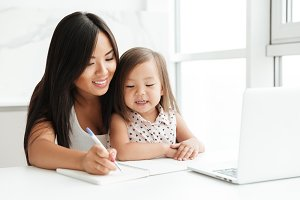 Mom with little cute asian girl using laptop writing notes