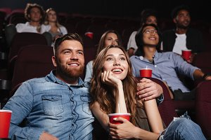 Happy young couple sitting at the cinema