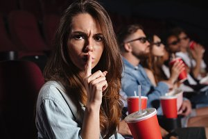 Lady sitting in cinema showing silence gesture.