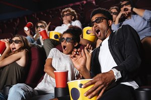 Scared young friends sitting in cinema watch film