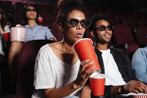 Serious young friends sitting in cinema watch film