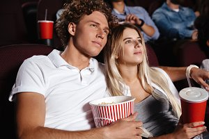 Concentrated young friends loving couple sitting in cinema