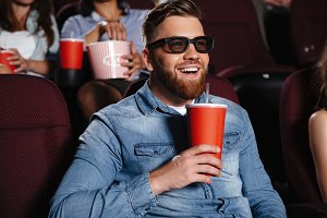 Concentrated young man sitting in cinema
